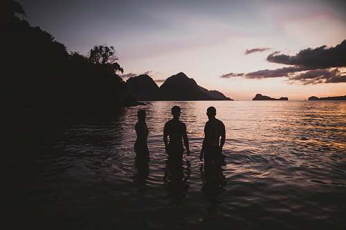 human silhouette of three person standing on calm body of water person