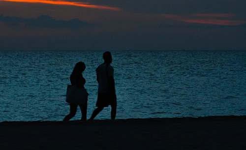 human silhouette of two person walking beside beach person