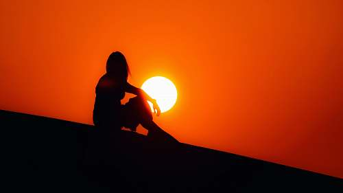 outdoors silhouette of woman sitting on ground sun