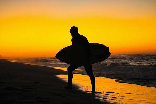 outdoors silhouette photography of man holding surfing board during golden hour ocean