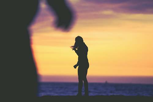 people silhouette photography of woman standing at beach human