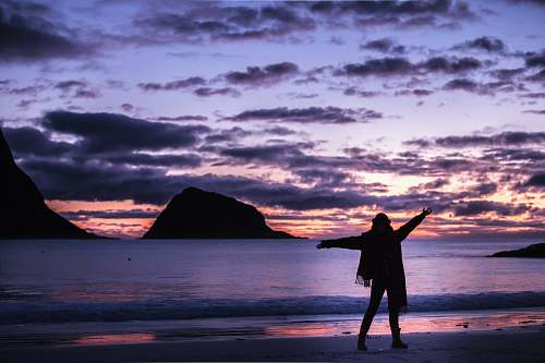 outdoors silhouette photography of woman standing on shore sea