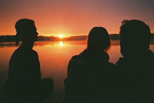 outdoors three people by a lake at sunset human