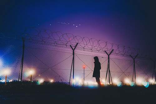 silhouette person's silhouette standing near chain link fence night light