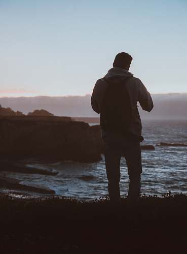 nature man standing beside body of water ocean