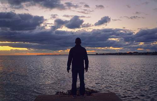 person man standing in front of sea human