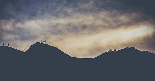 nature silhouette of people crossing a mountain cloud