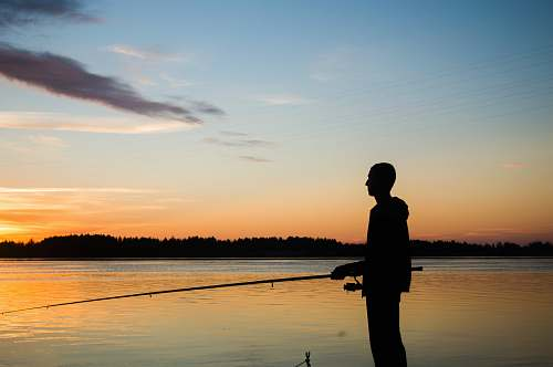 human silhouette of person fishing water