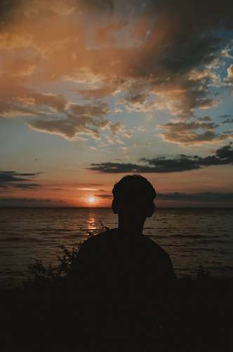 nature silhouette photography of person standing beside body of water sunset
