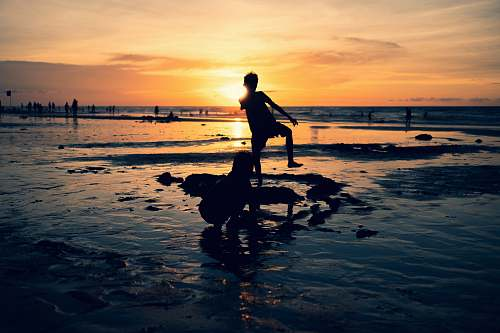 nature silhouette photography of toddler standing outdoors ocean