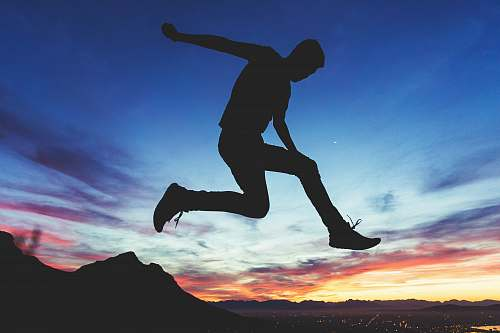 silhouette silhouette of man jumping near mountain cape town