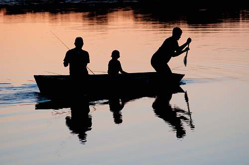 person silhouette of three person riding on boat on body of water human