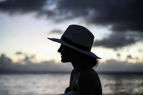 hat silhouette of woman standing beside body of water cowboy hat
