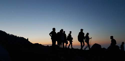 photo person silhouette on people standing on mountain during blue hour human free for commercial use images