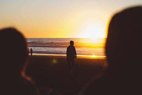 waves silhouette photo of man standing near seashore at sunset ocean