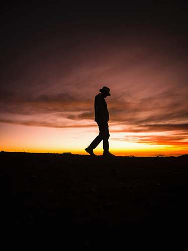 person silhouette photography of man wearing fedora hat human