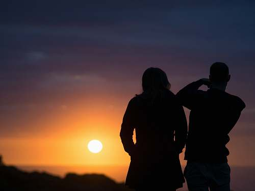 human man and woman silhouettes during golden hour people