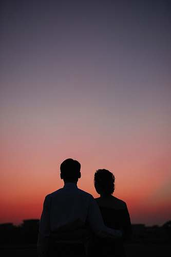 silhouette man and woman standing and looking sunset nature