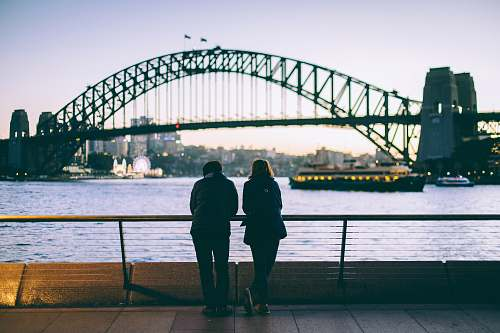 human man and woman standing beside each other in front of body of water people