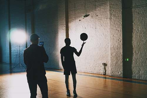 human man capturing silhouette photo of man spinning basketball people