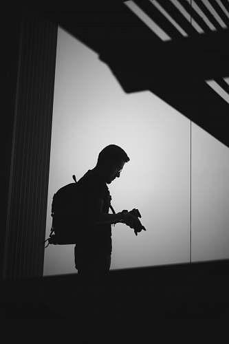 grey man holding camera black-and-white