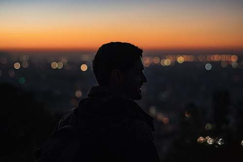 human man on high ground facing right looking at city during nighttime people