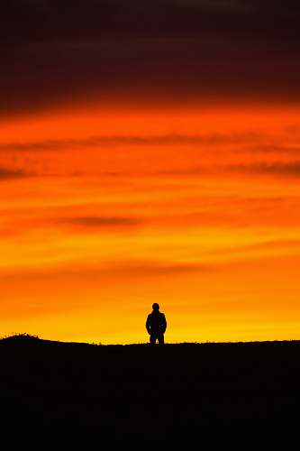 silhouette man standing at peak at golden hour nature