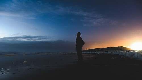 silhouette man standing on seashore facing sea people
