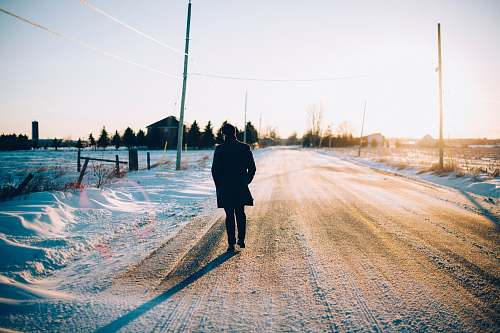 human man walking in the middle of the road covered with snow people