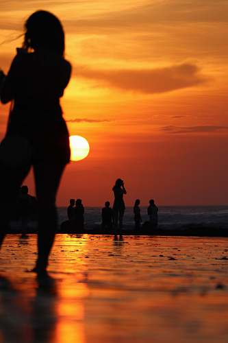 human people at the beach during golden hour sunset