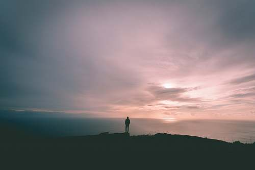 nature person standing on hill under gray sky outdoors