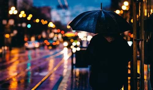 city person walking on street while holding black umbrella near cars on road at nighttime rain