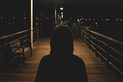 human person wearing hooded jacket walking in bridge people