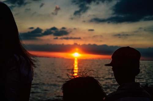 human silhouette of children looking on orange sunset above sea people