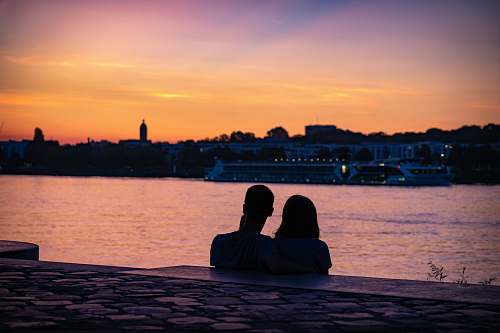 human silhouette of couple sitting on shore looking at city skyline during sunset sitting
