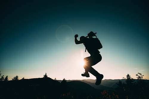 human silhouette of jumping person on hill people