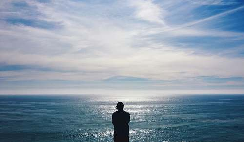 human silhouette of man facing the sea standing