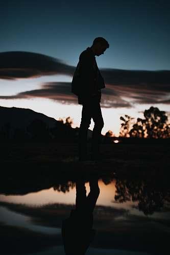 people silhouette of man near body of water human