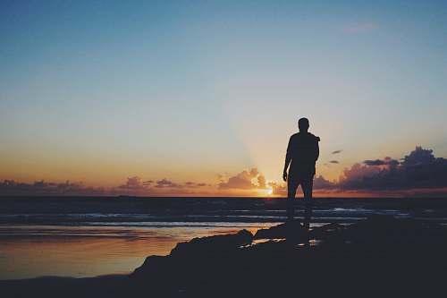 people silhouette of man standing near shoreline human