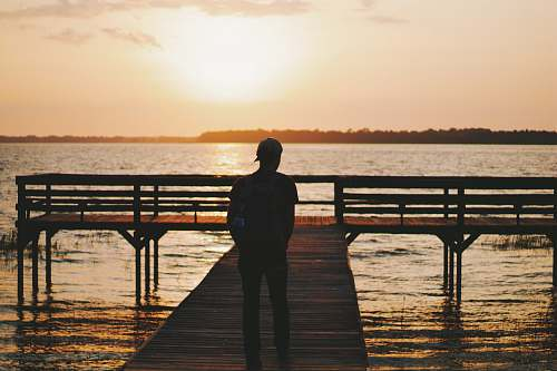 people silhouette of man walking on dock during golden hour water