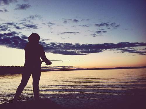 silhouette silhouette of person holding fishing rod taken at sunset human