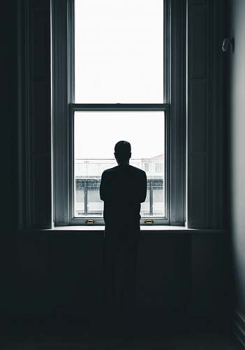 human silhouette of person standing in front of window at daytime people