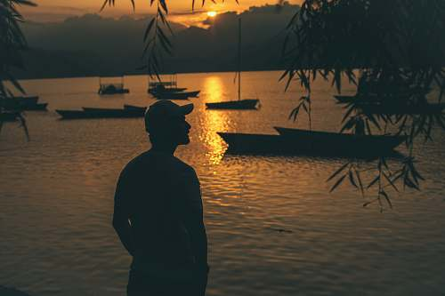 human silhouette of person standing near body of water and boats on body of water nature