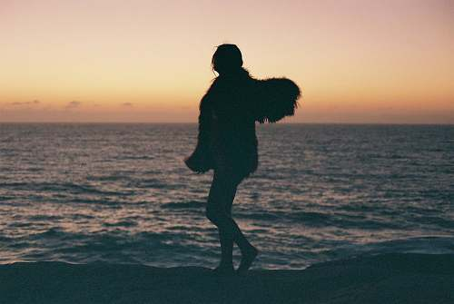 human silhouette of person standing near seashore people