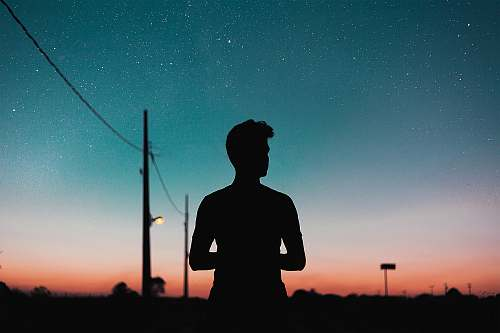 human silhouette of person standing near utility pole during night nature