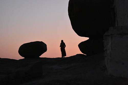 human silhouette of person standing on high ground beside large rock nature
