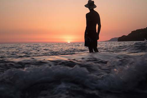 human silhouette of person standing on shallow seashore facing sunset people