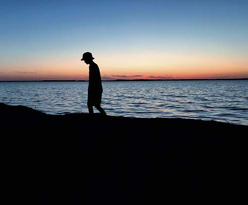 human silhouette of person walking near body of water standing