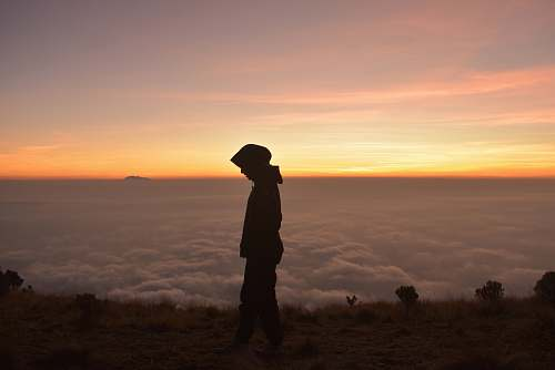 human silhouette of person wearing hoodie standing near cliff with clouds ahead during golden hour people