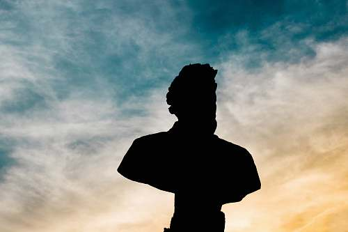human silhouette of statue bust of man under cloud sky during daytime people
